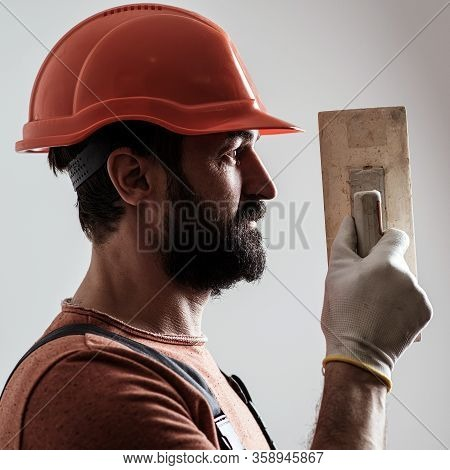 Plasterer Renovating Wall. Profile Of Bearded Builder. Worker With Wall Plastering Tools. Renovating
