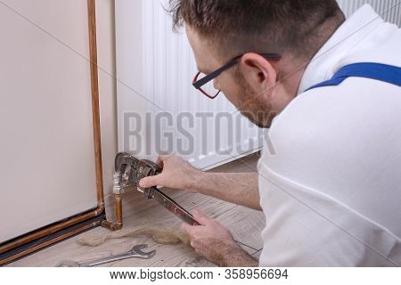 Plumber Holds The Adjustable Wrench And Adjusts The Tool Spacing. Screwing The Connection Screw From