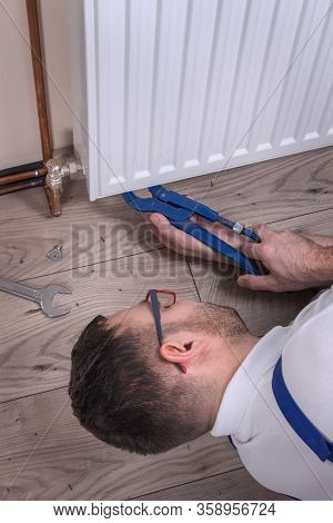 The Plumber Lies On The Floor And Screws The Valve Under The Radiator With An Adjustable Wrench. Spe
