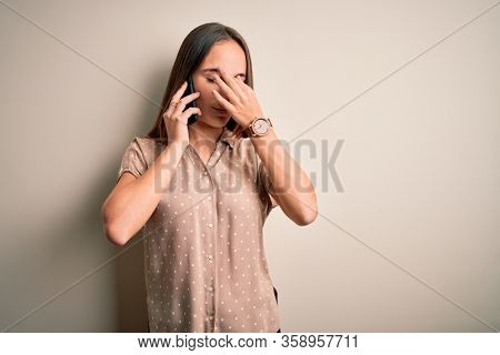 Young beautiful woman having conversation talking on the smartphone over white background tired rubbing nose and eyes feeling fatigue and headache. Stress and frustration concept.