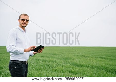 Young Agronomist Holds Tablet Touch Pad Computer In Green Wheat Field. Agribusiness Concept. Agricul