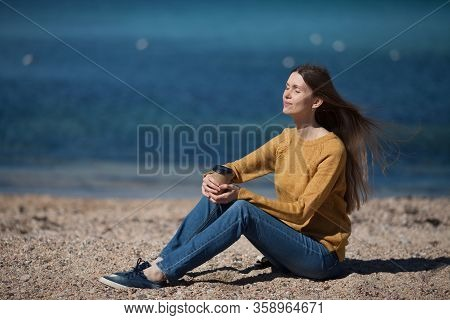 Beautiful Cute Girl Sitting On The Beach Near The Sea And Drinking Coffee To Take Away . The Concept