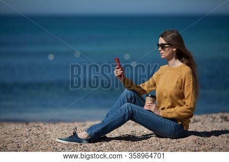A Beautiful Young Woman Is Texting On Her Smartphone On The Beach By The Sea. The Concept Of Technol