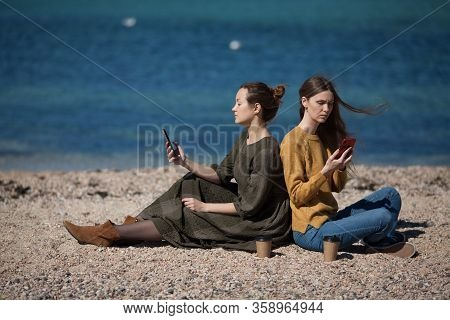 Two Friends Of The Girl Write Sms Each On Their Smartphone On The Beach By The Sea. The Concept Of M
