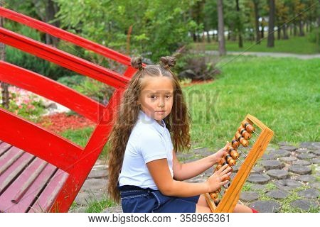 Portrait Of Beautiful Young First-grader Girl With Large Abacus. Thoughtful Schoolgirl Using A Maths