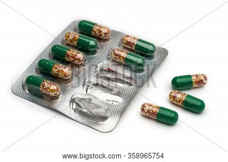 Isolate. Seven Capsules In Blister Packs And Three Unpacked. The Capsules Are Half Green And Transpa