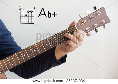 Learn Guitar - Man In A Dark Blue Shirt Playing Guitar Chords Displayed On Whiteboard, Chord A Flat+