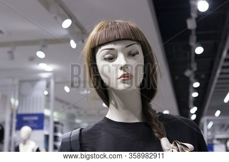 Female Mannequin With Long Hair And Bangs, Long Eyelashes, Make-up Dressed In Casual Clothes On A Bo