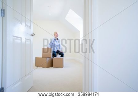 Senior Woman Downsizing In Retirement Sitting On Boxes In New Home On Moving Day