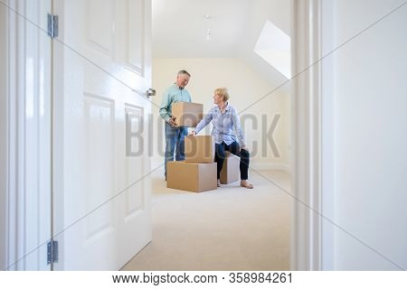 Senior Couple Downsizing In Retirement Carrying Boxes Into New Home On Moving Day