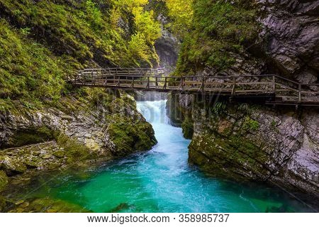 On the slopes of the gorge laid wooden walkways with railings. Vintgar gorge. Sunset illuminates mountain river with azure water. Wooden bridge. Slovenia. The concept of active and photo tourism