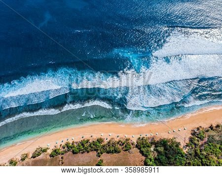 Aerial Photo Of A Wild Beach In Bali. A Row Of Sun Umbrellas On The Beach. Wild Beach In Bali With Y
