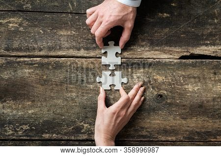 Top View Of Male And Female Hand Joining Two Matching Puzzle Pieces Over Rustic Wooden Background.
