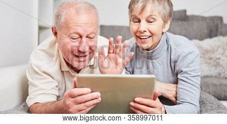 Happy senior couple having video chat with tablet computer in living room