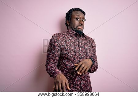 Young handsome african american man wearing casual shirt standing over pink background disgusted expression, displeased and fearful doing disgust face because aversion reaction.