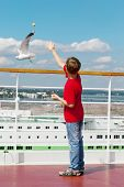 Boy in red t-shirt feeds seagulls with pieces of bread on deck of cruise  ship. poster
