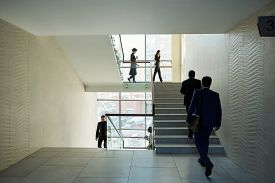 Large group of young contemporary office managers going upstairs and downstairs in the middle of working day in business center