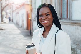 Close Up Portrait Of A Beautiful Young African American Woman With Pigtails In A White Jacket And Br