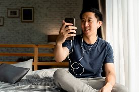 Portrait Of Happy 30s Aged Asian Man In Casual Clothing Making Facetime Video Calling With Smartphon