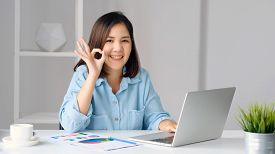 Work From Home, Happy Asian Women Working With Laptop Computer At Home Office And Showing Ok Hand Si