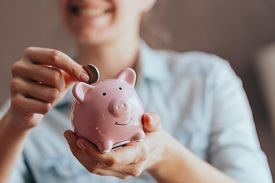 Female Hands Hold A Pink Piggy Bank And Puts A Coin There. The Concept Of Saving Money Or Savings, I