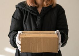 Girl Courier Holds A Parcel In Protective Gloves. Epidemic. Close-up.
