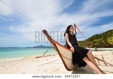 happy young girl sit on boat on white beach