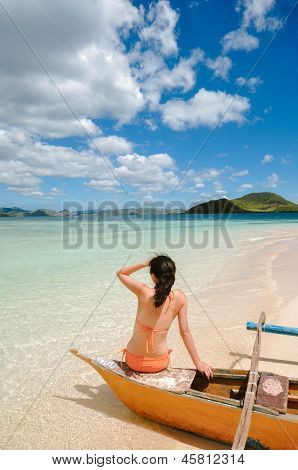 young girl sitting on boat on beach