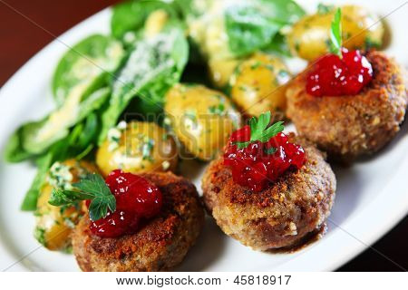 A picture of traditional Polish meatballs served with spring potatoes and spinach
