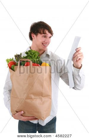 Smiling Young Man Holding Groceries Paper Bag And Receipt