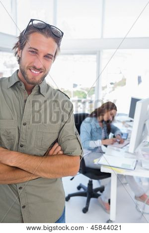 Man smiling in creative office with arms folded and partner working behind