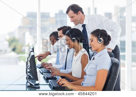 Manager explaining something to his employee in a call centre