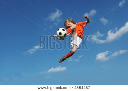 Healthy Child Playing Football Kicking Ball In Midair