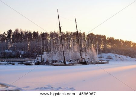 Old fisher boat sunk and frozen in a small sea harbor. poster