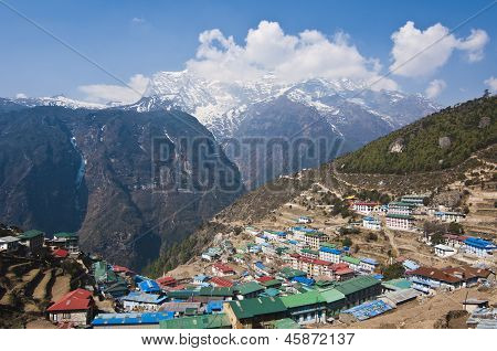 Namche Bazaar, the transit town for trekkers and mountaineers in Nepal's Everest Region offers an incredibly beautiful sight from a higher point sitting on a bowl shaped landscape with the Kongde Range in the background poster