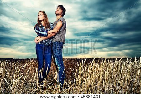 Romantic young couple in casual clothes standing together in a wheat field on a background of the storm sky.