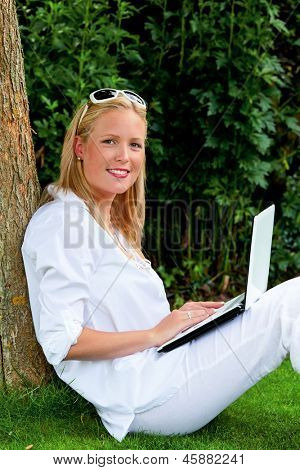 a young woman sitting with a laptop computer in the garden and surfs the internet. wi-fi in the park