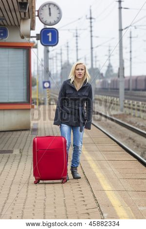 a young woman with suitcase waiting on the platform of a railway station on their train. train delays