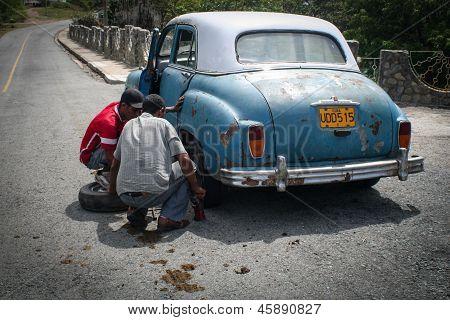 Young Men Changing Tyre In Siboney, Cuba