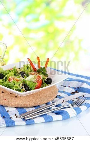 Light salad on plate on napkin on window background poster