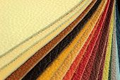 Natural leather upholstery samples with stitching in various colors. poster