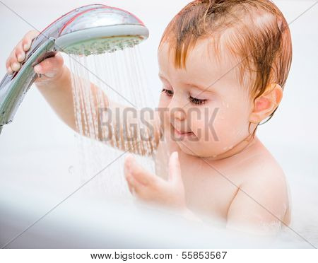 cute 1 year-old girl bathes in a shower