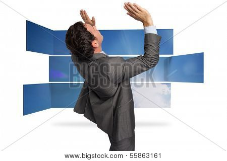 Businessman standing with arms pressing up against structure showing sky