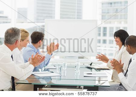 Business people clapping at blank whiteboard in conference room in the office