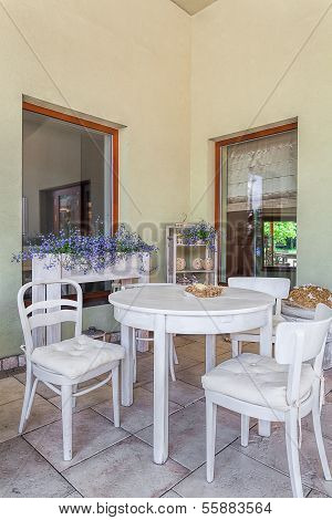 Mediterranean interior - an outdoors dining room with white furniture poster