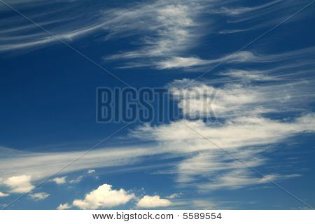 Wind Blown Clouds On Blue Sky