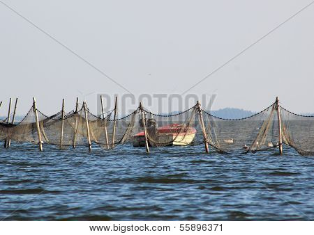 Small Boat Near Offshore Fishing Net And Traps