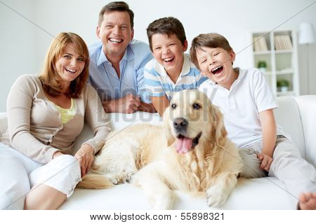 Portrait of happy family with their pet having good time at home