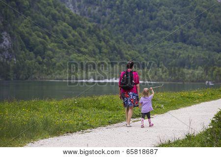 Women And Child Walks Along The Lake