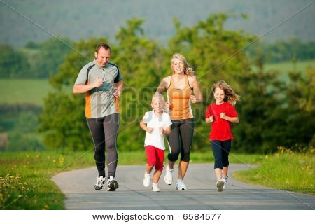 Family jogging outdoors with the kids in a beautiful summer landscape in the late afternoon sun poster